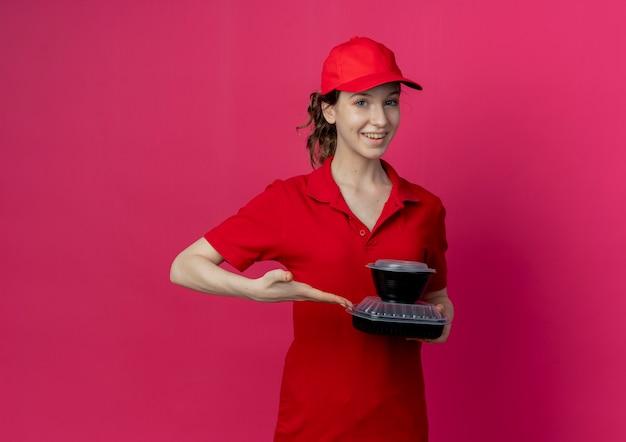 Lächelndes junges hübsches liefermädchen, das rote uniform und kappe hält und mit hand auf lebensmittelbehälter lokalisiert auf purpurrotem hintergrund mit kopienraum zeigt