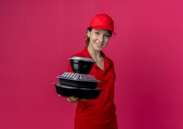 Lächelndes junges hübsches liefermädchen, das rote uniform und kappe trägt, die lebensmittelbehälter in richtung kamera ausstatten, die auf purpurrotem hintergrund mit kopienraum isoliert wird
