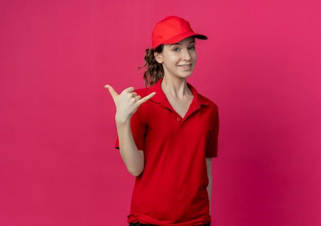 Lächelndes junges hübsches liefermädchen in der roten uniform und in der kappe, die lose geste hängen, lokalisiert auf purpurrotem hintergrund mit kopienraum