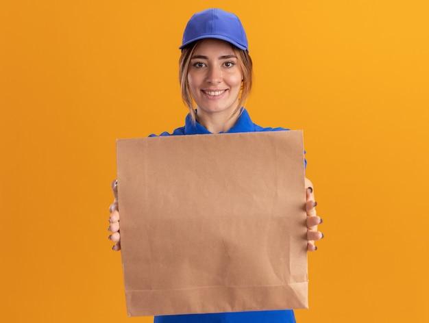 Lächelndes junges hübsches liefermädchen in der uniform, die papiernahrungsmittelpaket auf orange hält