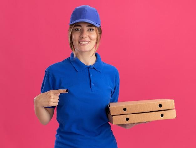 Lächelndes junges hübsches liefermädchen in uniform hält und zeigt auf pizzaschachteln auf rosa