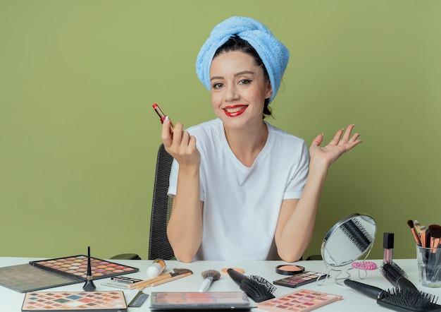 Lächelndes junges hübsches mädchen, das am make-up-tisch mit make-up-tools und mit handtuch auf dem kopf sitzt, lippenstift hält und leere hand auf olivgrünem grün zeigt