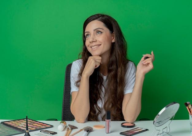 Lächelndes junges hübsches mädchen, das am make-up-tisch mit make-up-werkzeugen hält, die wimperntusche halten kinn berühren und seite lokalisiert auf grünem hintergrund betrachten