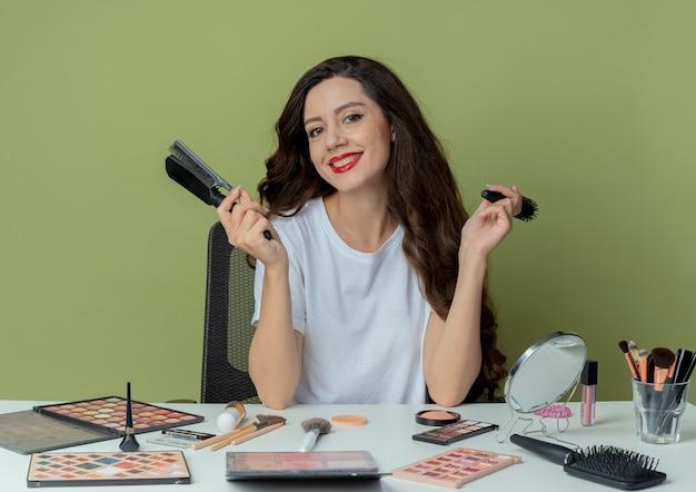 Lächelndes junges hübsches mädchen, das am make-up-tisch mit make-up-werkzeugen sitzt, die kämme lokalisiert auf olivgrünem hintergrund halten