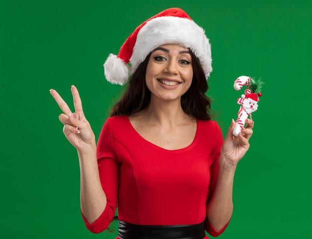 Lächelndes junges hübsches mädchen, das weihnachtsmütze hält, die zuckerstangenverzierung betrachtet, die kamera tut, die friedenszeichen lokalisiert auf grünem hintergrund tut