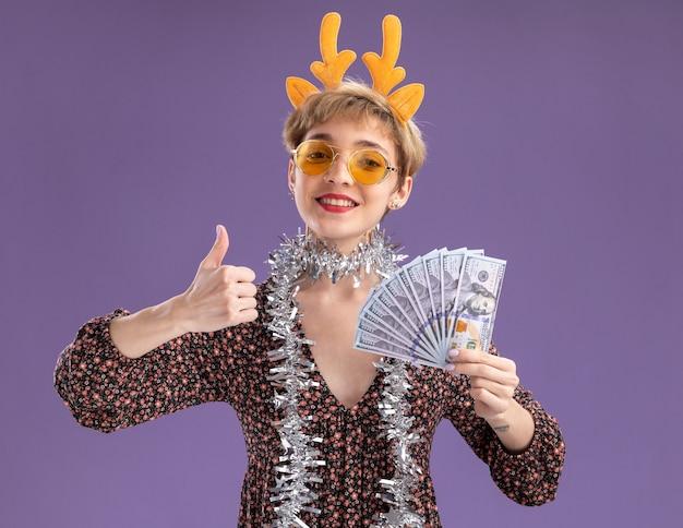 Lächelndes junges hübsches mädchen mit rentiergeweih-stirnband und lametta-girlande um den hals mit brille, die geld hält, das den daumen isoliert auf lila wand zeigt