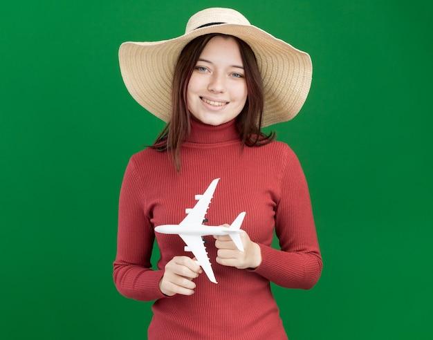 Lächelndes junges hübsches mädchen mit strandhut, das modellflugzeug isoliert auf grüner wand mit kopienraum hält