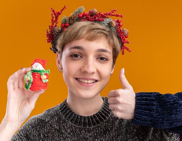 Lächelndes junges hübsches mädchen mit weihnachtskopfkranz, der eine kleine weihnachtsschneemannstatue hält, die daumen nach oben isoliert auf oranger wand zeigt