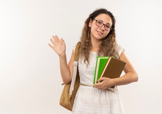 Lächelndes junges hübsches schulmädchen, das brille und rückentasche hält bücher hält und vorne lokalisiert auf weißer wand winkt