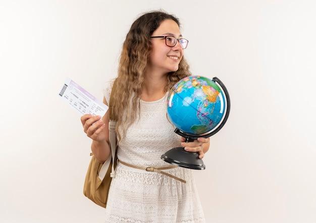 Lächelndes junges hübsches schulmädchen, das brille und rückentasche trägt globus und tickets hält und seite lokalisiert auf weißer wand betrachtet