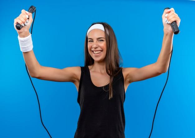 Lächelndes junges hübsches sportliches mädchen, das stirnband und armband hält, das springseil lokalisiert auf blauem raum hält