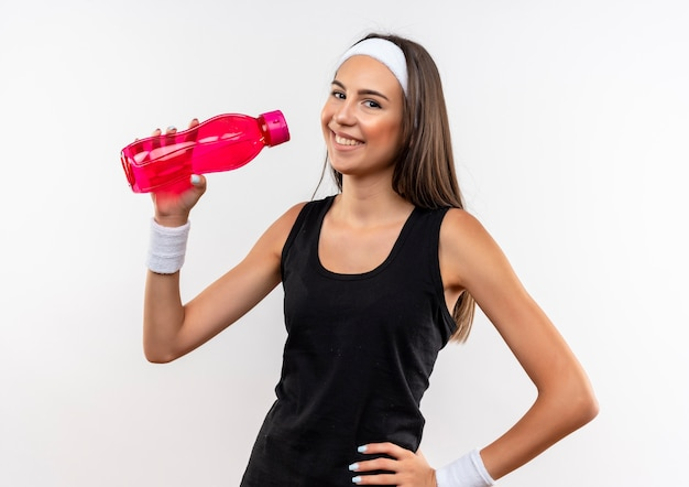 Lächelndes junges hübsches sportliches mädchen, das stirnband und armband hält wasserflasche mit hand auf taille auf weißem raum hält