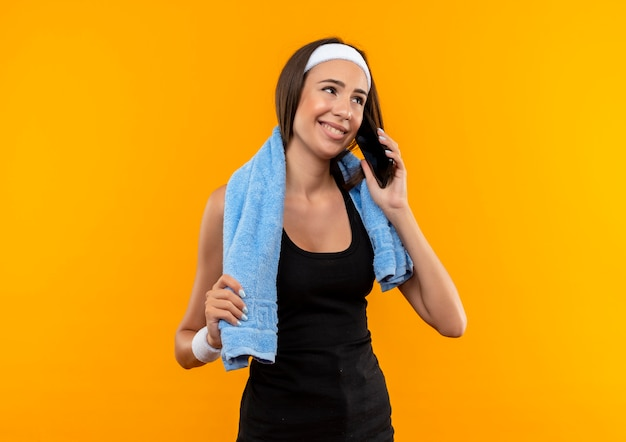 Lächelndes junges hübsches sportliches mädchen, das stirnband und armband mit handtuch um ihren hals auf orange raum trägt