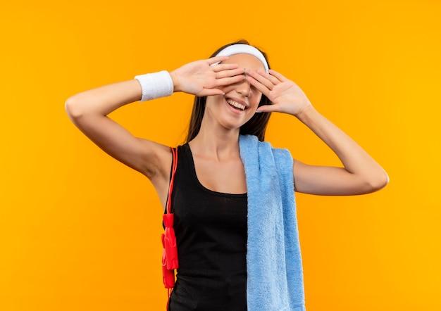 Lächelndes junges hübsches sportliches mädchen, das stirnband und armband mit handtuch und springseil auf ihren schultern trägt und augen mit händen auf orange raum schließt