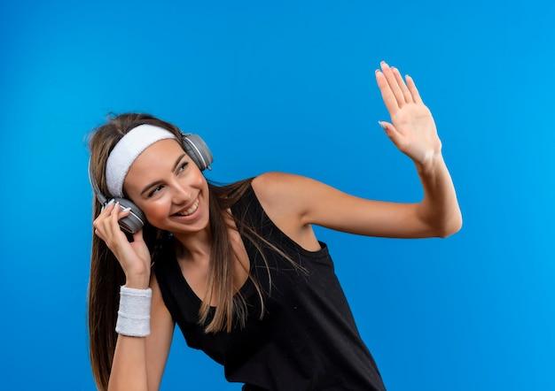 Lächelndes junges hübsches sportliches mädchen, das stirnband und armband und kopfhörer trägt, die zur seite schauen und mit einer hand auf kopfhörer lokalisiert auf blauem raum winken