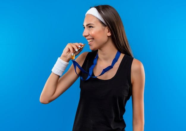 Lächelndes junges hübsches sportliches mädchen, das stirnband und armband und medaillen um den hals trägt, die seite betrachten und versuchen, medaille isoliert auf blauem raum zu beißen