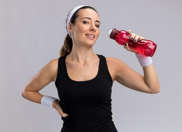 Lächelndes junges hübsches sportliches mädchen mit stirnband und armbändern, das eine wasserflasche hält und die hand an der taille hält, isoliert auf weißer wand