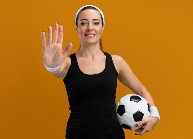Lächelndes junges hübsches sportliches mädchen mit stirnband und armbändern, das fußball hält und stop-geste macht