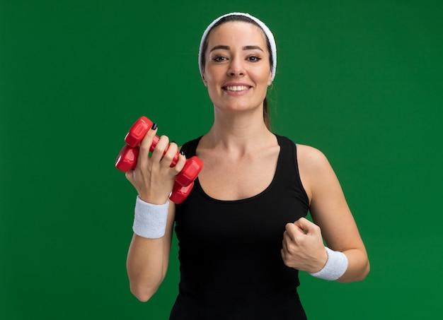 Lächelndes junges hübsches sportliches mädchen mit stirnband und armbändern mit hanteln
