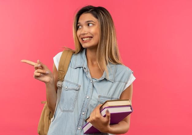 Lächelndes junges hübsches studentenmädchen, das rückentasche hält, die bücher sucht und auf seite lokalisiert auf rosa wand hält