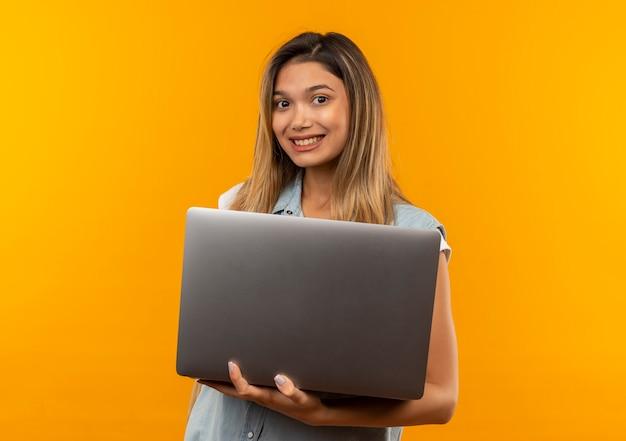 Lächelndes junges hübsches studentenmädchen, das rückentasche hält laptop lokalisiert auf orange wand trägt