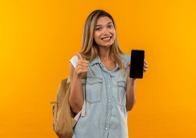 Lächelndes junges hübsches studentenmädchen, das rückentasche trägt, die handy und daumen oben auf orange wand lokalisiert zeigt