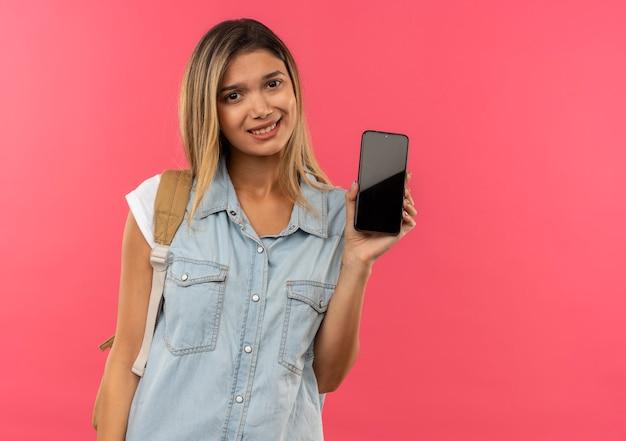Lächelndes junges hübsches studentenmädchen, das rückentasche zeigt handy zeigt, das auf rosa wand lokalisiert wird
