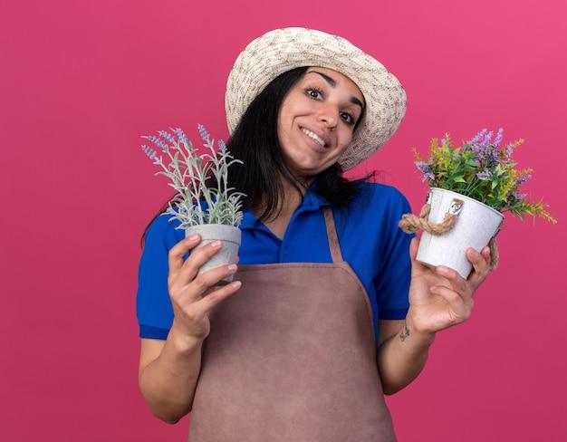 Lächelndes junges kaukasisches gärtnermädchen in uniform und hut, das blumentöpfe isoliert auf rosa wand hält