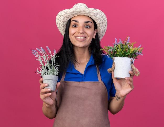 Lächelndes junges kaukasisches gärtnermädchen in uniform und hut mit blumentöpfen