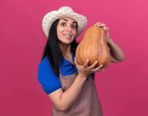 Lächelndes junges kaukasisches gärtnermädchen in uniform und hut mit butternut-kürbis