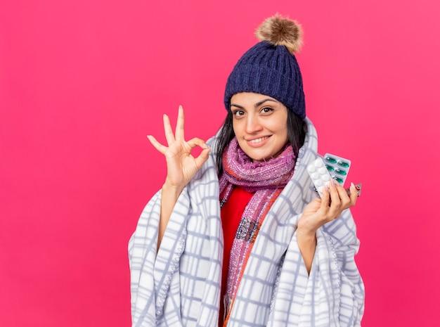 Lächelndes junges kaukasisches krankes mädchen, das wintermütze und schal trägt, die in plaid eingewickelt betrachten kamera, die packungen der pillen hält, die ok zeichen lokalisiert auf purpurrotem hintergrund mit kopienraum tun Kostenlose Fotos