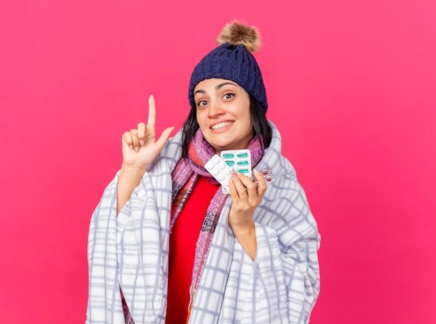 Lächelndes junges kaukasisches krankes mädchen, das wintermütze und schal trägt, eingewickelt in plaid, das packungen von medizinischen pillen hält, die lokal auf purpurroter wand mit kopienraum zeigen