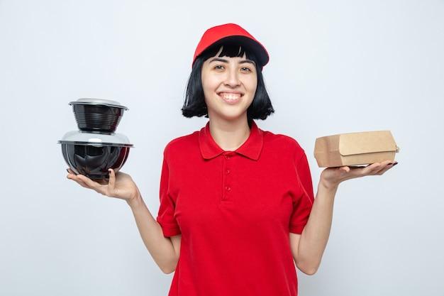 Lächelndes junges kaukasisches liefermädchen, das lebensmittelbehälter und papierverpackungen hält