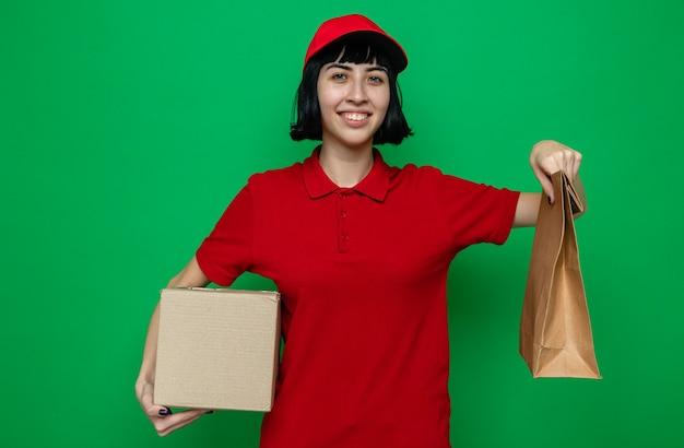 Lächelndes junges kaukasisches liefermädchen, das lebensmittelverpackungen und karton hält