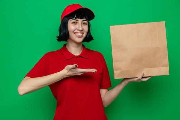 Lächelndes junges kaukasisches liefermädchen, das mit der hand auf papierlebensmittelverpackungen hält und zeigt
