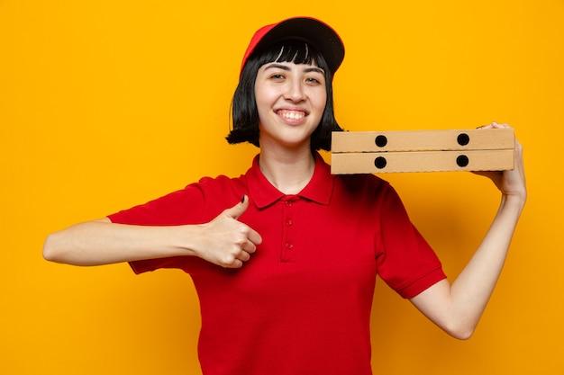 Lächelndes junges kaukasisches liefermädchen, das pizzakartons auf ihrer schulter hält und nach oben greift