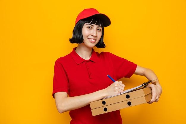 Lächelndes junges kaukasisches liefermädchen, das pizzakartons hält und in die zwischenablage schreibt