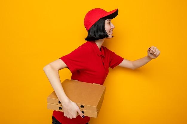 Lächelndes junges kaukasisches liefermädchen, das seitlich steht, pizzakartons hält und so tut, als würde es laufen