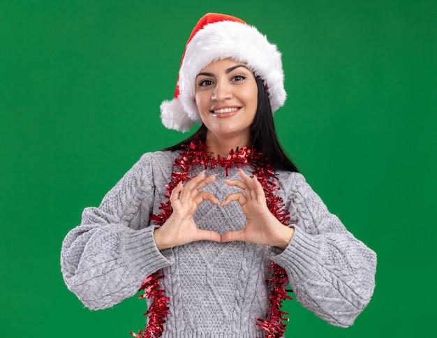 Lächelndes junges kaukasisches mädchen, das weihnachtshut und lametta-girlande um den hals trägt und kamera betrachtet, die herzzeichen lokalisiert auf grünem hintergrund tut