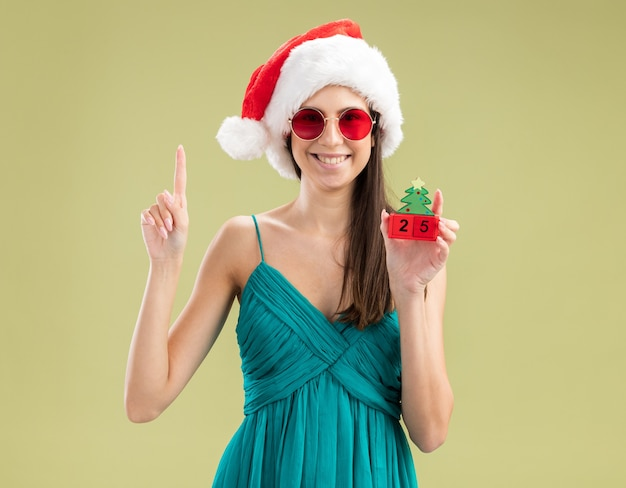 Lächelndes junges kaukasisches mädchen in der sonnenbrille mit der weihnachtsmütze, die weihnachtsbaumverzierung hält und nach oben zeigt
