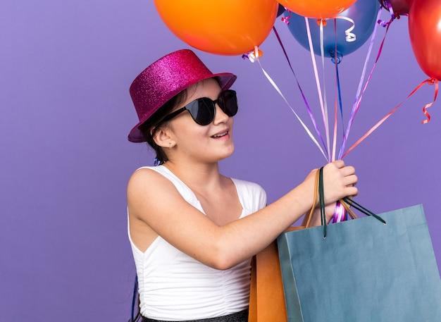 Lächelndes junges kaukasisches mädchen in sonnenbrille mit violettem partyhut, der einkaufstaschen hält und heliumballons betrachtet, die auf lila wand mit kopienraum isoliert werden
