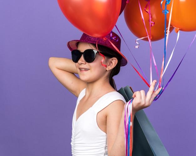 Lächelndes junges kaukasisches mädchen in sonnenbrille mit violettem partyhut, der heliumballons und einkaufstaschen auf schulter lokalisiert auf lila wand mit kopienraum hält