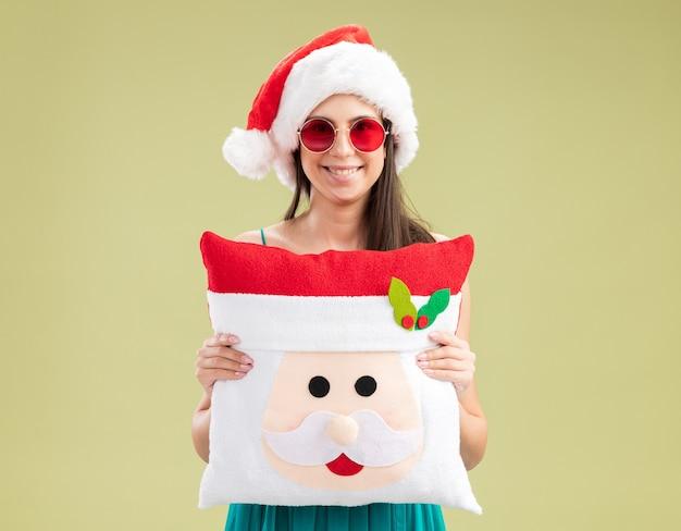Lächelndes junges kaukasisches mädchen in sonnenbrille mit weihnachtsmütze, die weihnachtsmannkissen hält
