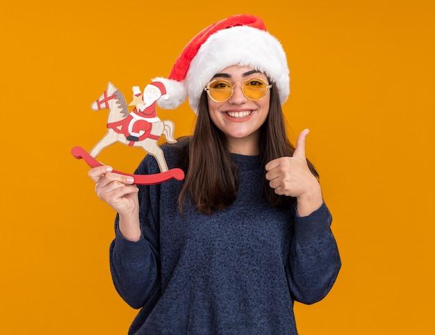 Lächelndes junges kaukasisches mädchen in sonnenbrille mit weihnachtsmütze hält den weihnachtsmann auf schaukelpferddekoration und daumen hoch isoliert auf orangefarbener wand mit kopierraum