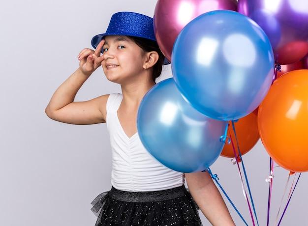 Lächelndes junges kaukasisches mädchen mit blauem partyhut, der heliumballons und gestikulierendes siegeshandzeichen lokalisiert auf weißer wand mit kopienraum hält