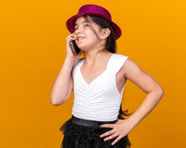 Lächelndes junges kaukasisches mädchen mit lila partyhut telefoniert isoliert auf oranger wand mit kopierraum