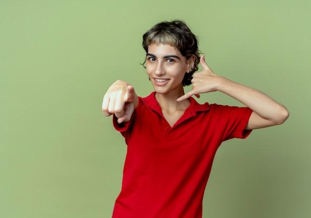 Lächelndes junges kaukasisches mädchen mit pixie-haarschnitt, der anrufgeste tut und auf kamera zeigt, die auf olivgrünem hintergrund mit kopienraum lokalisiert wird