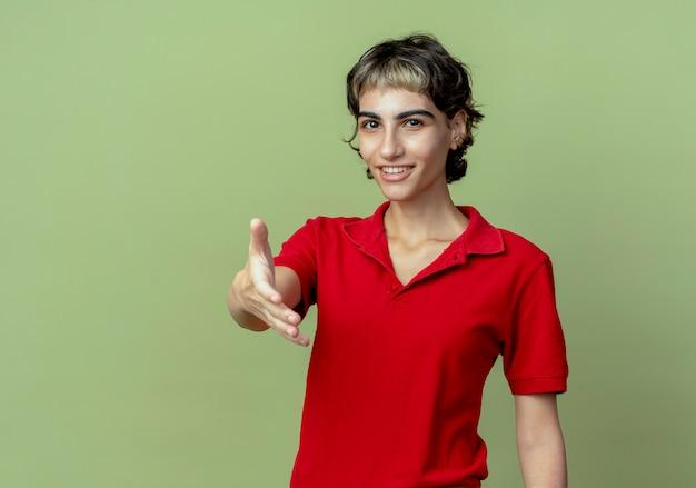 Lächelndes junges kaukasisches mädchen mit pixie-haarschnitt, der die hand gestikuliert, die hi lokalisiert auf olivgrünem hintergrund mit kopienraum ausstreckt
