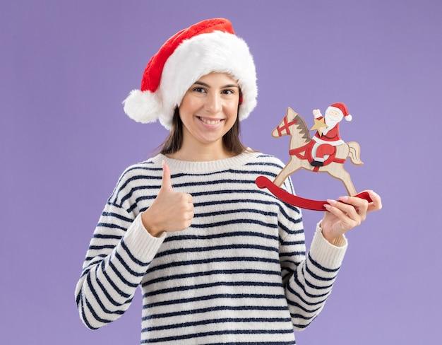 Lächelndes junges kaukasisches mädchen mit weihnachtsmütze hält den weihnachtsmann auf schaukelpferddekoration und daumen hoch isoliert auf lila wand mit kopierraum