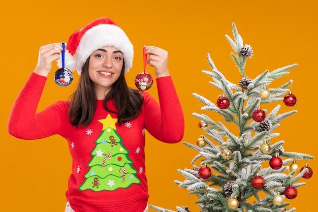 Lächelndes junges kaukasisches mädchen mit weihnachtsmütze hält glaskugelverzierungen, die neben weihnachtsbaum stehen, lokalisiert auf orange hintergrund mit kopienraum